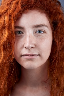 Caucasian red haired girl with freckles and green eyes