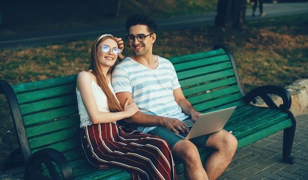 Кавказская рыжеволосая подруга с веснушками и очками сидит рядом со своим любовником на скамейке за ноутбуком