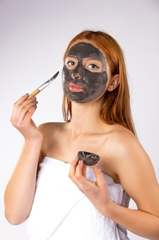 백인 redhaired 여자는 자연 브러시 흰색 벽으로 그녀의 얼굴에 검은 점토 마스크를 적용