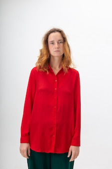 Caucasian redheaded woman with long hair in red shirt on white background