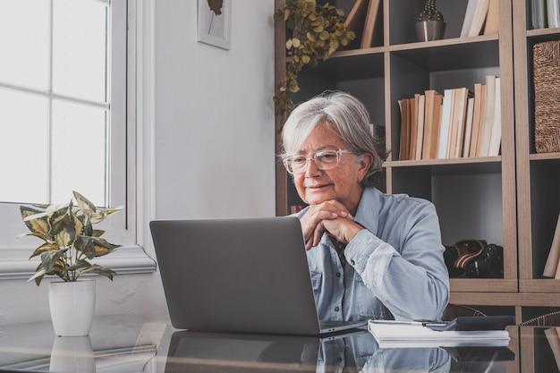 백인 반사적으로 노트북 화면을 보고, 일에 대해 생각하고, 어려운 프로젝트에서 독립적으로 일하는 여성 사업가입니다. 실내 사무실에서 집에서 준비하는 여성.