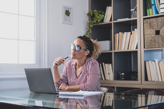 Caucasian reflexive looking at laptop screen, reflexing on work, businesswoman independent working in a difficult project. female person preparing at home in the office indoor.