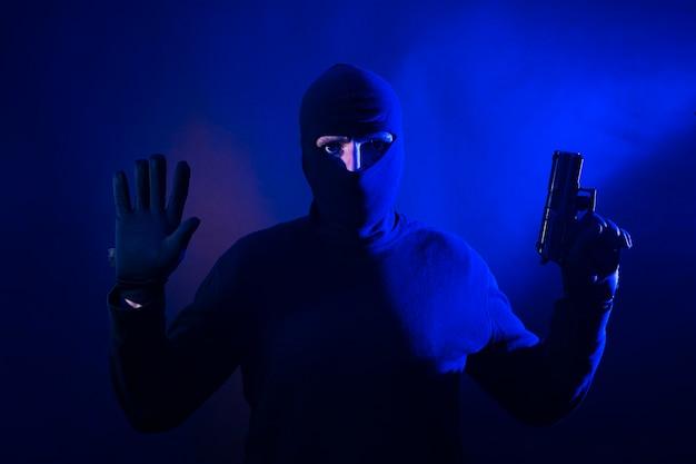上げられた手と銃を持つ白人強盗。警察のライトが含まれています。