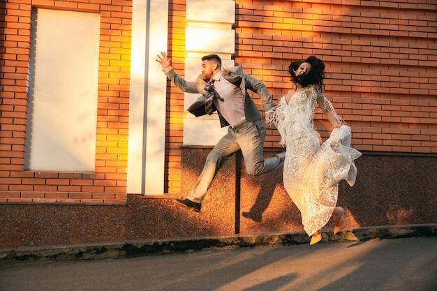 Giovani coppie romantiche caucasiche che celebrano il matrimonio in città. tenera sposa e sposo sulla strada della città moderna. famiglia, relazione, concetto di amore