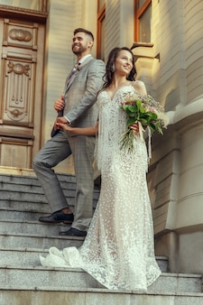 Caucasian romantic young couple celebrating their marriage in city. tender bride and groom on modern city's street. family, relationship, love concept