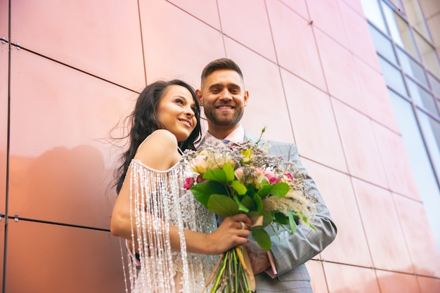Caucasian romantic young couple celebrating their marriage in city.