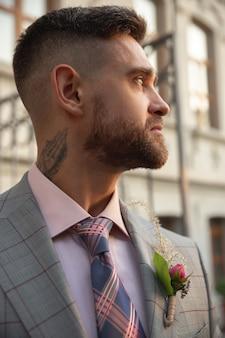 Giovane sposo romantico caucasico che celebra il matrimonio in città. uomo alla moda sulla strada della città moderna. famiglia, relazione, concetto di amore. matrimonio contemporaneo
