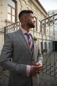 백인 로맨틱 젊은 신랑 도시에서 결혼을 축하. 현대 도시의 거리에 세련된 남자. 가족, 관계, 사랑 개념. 현대 결혼식. 행복하고 중요한 순간을 느낍니다. 세부.