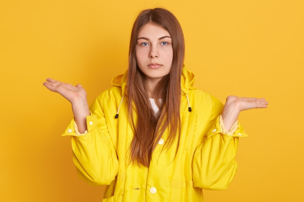 Caucasian sad woman spreading hands aside, showing helpless gesture, lady wearing jacket, posing against yellow wall, has serious look,  with upset expression.