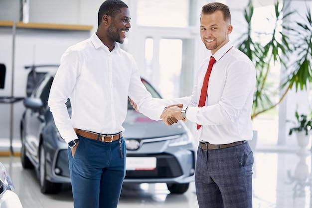 白人の販売代理店とディーラーで握手するアフリカの顧客の男性