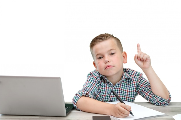 Caucasian school-age boy in a plaid shirt on an isolated background with a laptop and a phone records thoughts in a piece of paper.