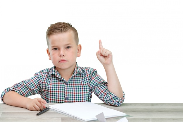 Caucasian school-age boy in a plaid shirt on an isolated background writes thoughts in a sheet.