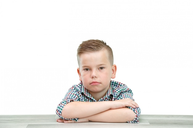 Caucasian school-age boy in a plaid shirt on a light isolated background sitting with his hands folded