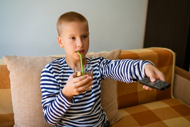 Кавказский школьник сидит на диване в повседневной одежде с пультом в руке и переключает ...