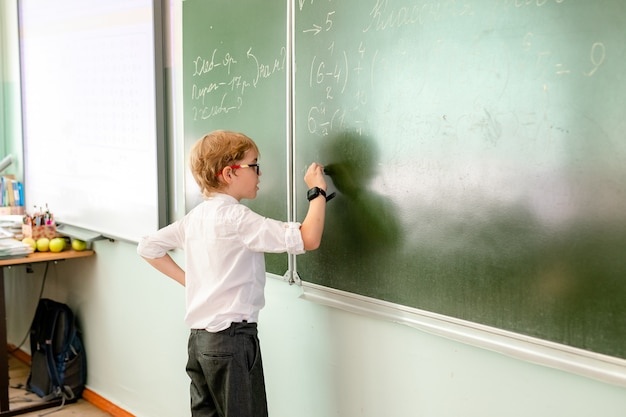 Caucasian schoolboy doing exercise at blackboard in classroom.