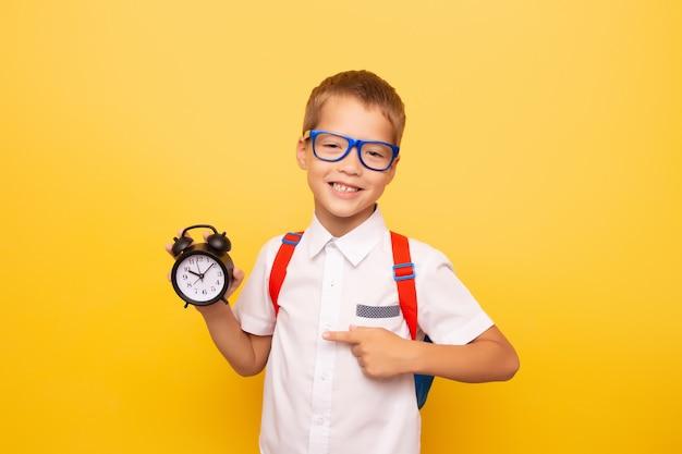 Кавказский школьник в белой рубашке и очках с рюкзаком держит будильник в руке и указывает на него пальцем и улыбается на желтом фоне. концепция дедлайнов, снова в школу.