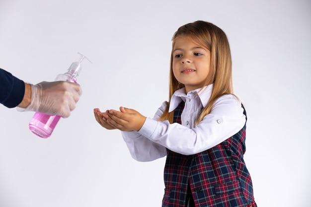 백인 여학생은 흰 벽에 고립 된 교실에 들어가기 전에 그녀의 손을 소독합니다. 바이러스 및 유행병 개념.