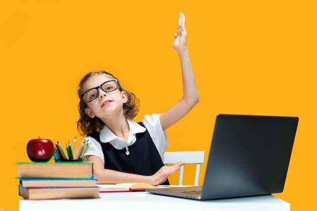 白人の女子高生は、オンラインレッスンの遠方の学校の学習中にラップトップに座って手を上げます