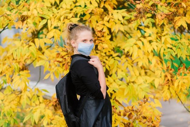 秋の風景の背景に顔を保護する医療マスクの白人女子高生ティーンエイジャー