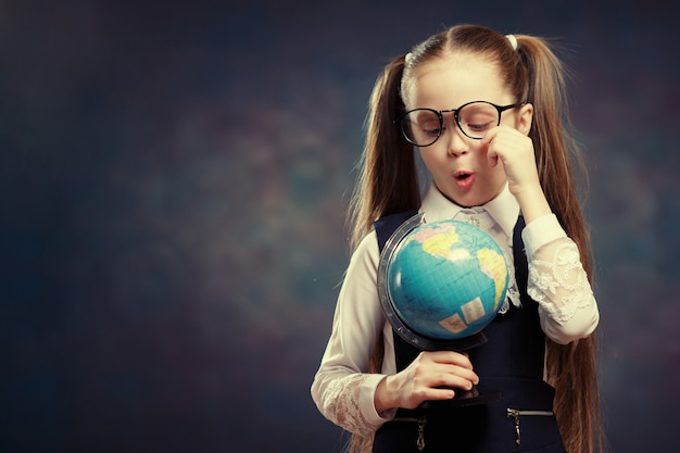 Caucasian schoolgirl wear glasses turn world globe.