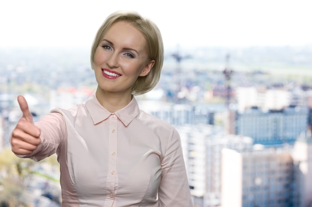 Caucasian secretary is showing like gesture. mature woman dressed in white bluse is smiling. blurred high-rise building on the background.