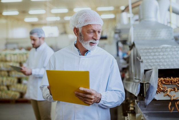 Caucasian senior adult quality controller holding folder with documents and checking on quality of salty sticks. food plant interior.