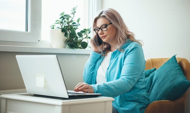 Caucasian senior businesswoman with glasses and blonde hair is talking on phone while working remotely with a laptop