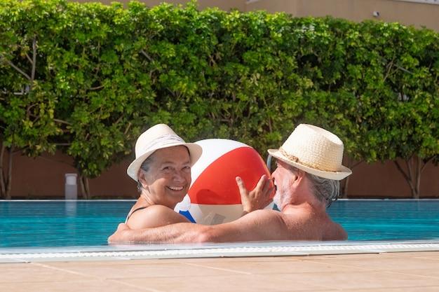 큰 풍선 공을 들고 수영장에 떠 있는 백인 수석 부부. 두 명의 행복한 은퇴자는 태양 아래서 여름 휴가를 즐긴다