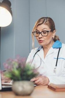 Кавказский старший врач в очках работает в офисе на ноутбуке в медицинских инструментах и одежде