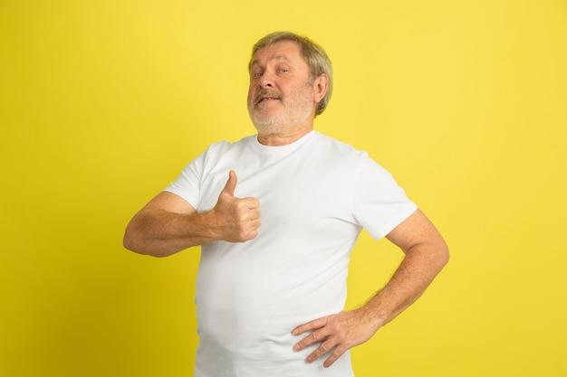 黄色のスタジオの壁に分離された白人の年配の男性の肖像画