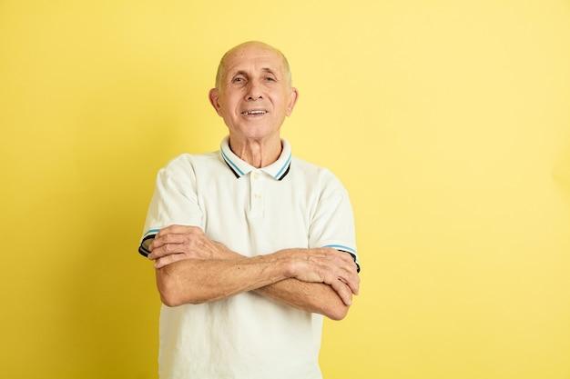 노란색 스튜디오에 고립 된 백인 수석 남자의 초상화