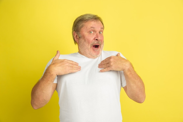 Caucasian senior man's portrait isolated on yellow