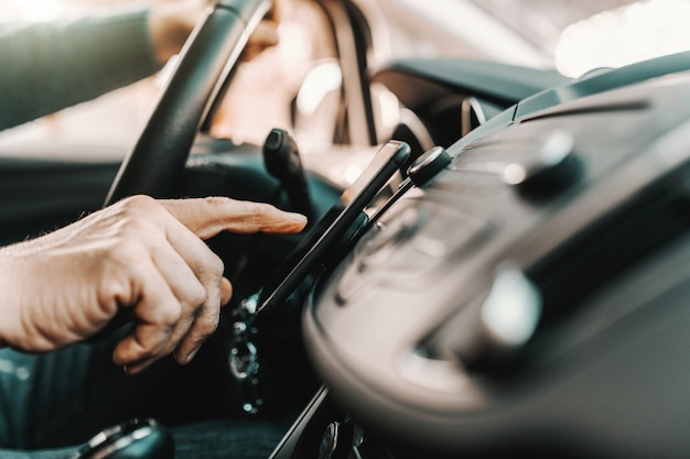 白人の年配の男性が彼の車に座っている間スマートフォンでナビゲーションをオンにします。