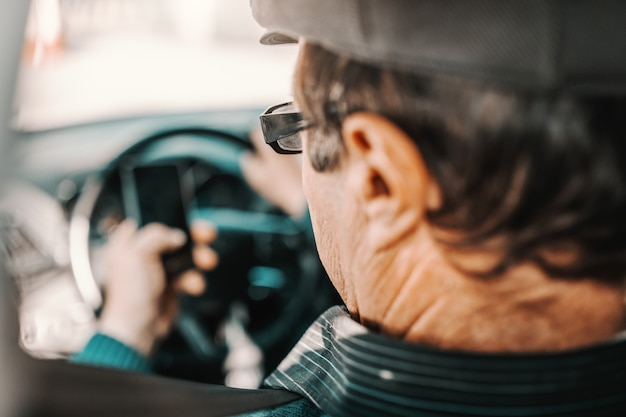 Caucasian senior man with cap on head and eyeglasses sitting in car with hand on steering wheel and using smart phone.