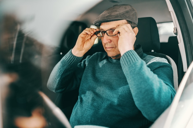 Caucasian senior man with cap on head putting eyeglasses while sitting in a car