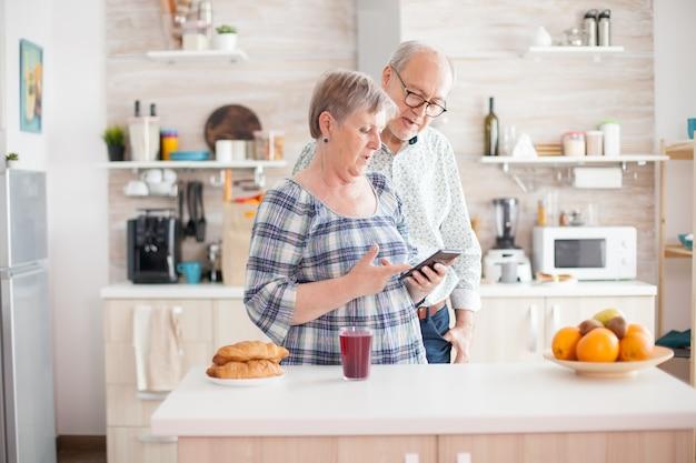 Кавказский старший жена и муж на кухне во время завтрака с помощью технологии смартфона и подключения к интернету. досуг пенсионерка и мужчина улыбается в доме, расслабляясь.