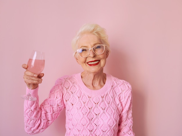 Caucasian senior woman in cashmere pink sweater drinking rose on pink background