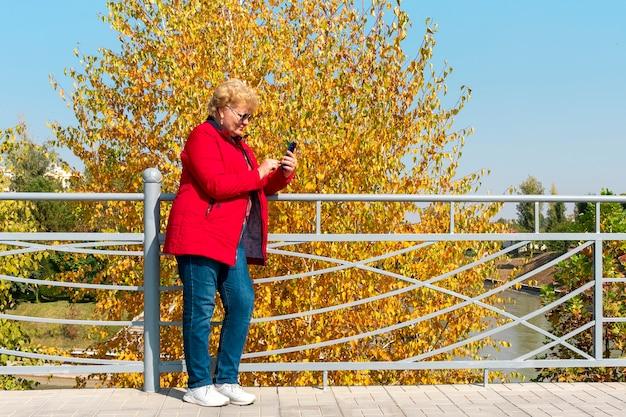 公園でスマートフォンを使用して赤いジャケットを着た白人の年配の女性