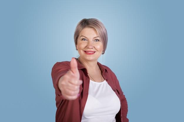 Кавказская старшая женщина, продвигающая что-то на синей стене, жестикулирующая знаком и улыбаясь