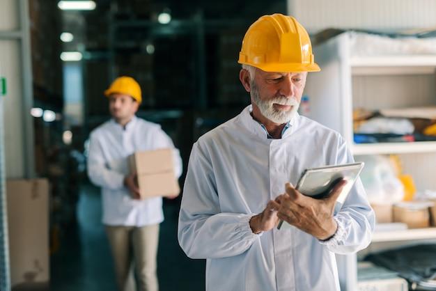 스토리지에 서있는 동안 태블릿을 사용 하여 백인 수석 노동자.