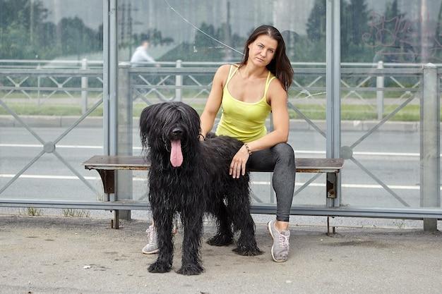 백인 심각한 소녀와 그녀의 검은 털복숭이 브리아 드는 대중 교통 역에 앉아 버스를 기다리고 있습니다.