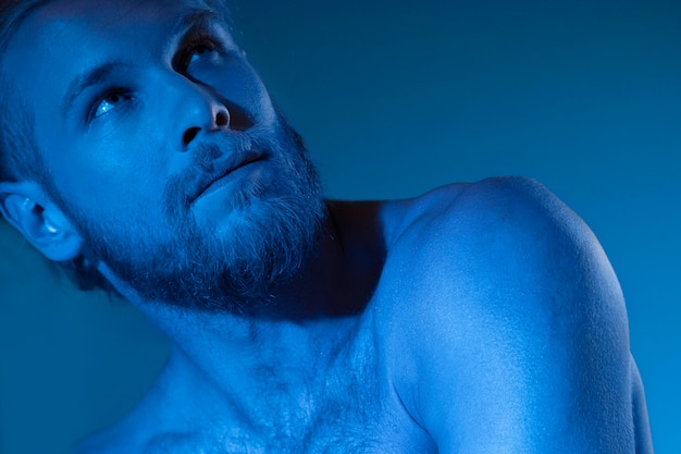 Caucasian shirtless man in blue tones
