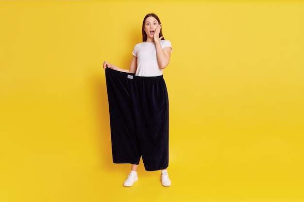 Caucasian shocked female with dark hair looking at camera with big eyes and open mouth, covering cheek with palm, wearing too big pants, woman lost weight, isolated over yellow wall.