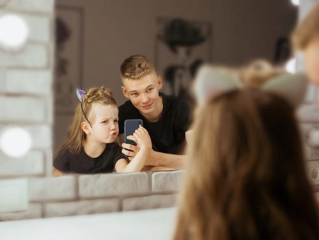 メイクアップルームで自分撮りをしている白人の兄弟の兄と妹