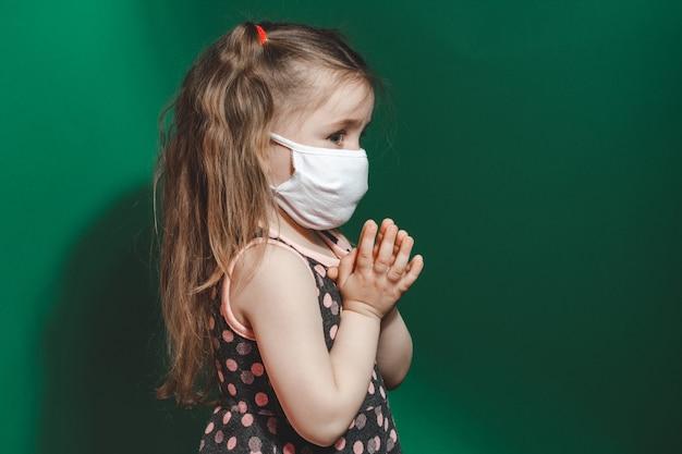 Кавказская больная маленькая девочка в медицинской маске во время эпидемии коронавируса молится на зеленом фоне крупным планом 2021 года.