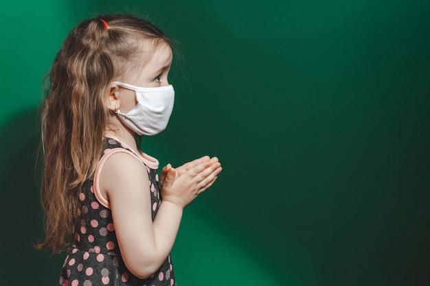 코로나 바이러스 전염병 동안 의료 마스크에 백인 아픈 어린 소녀는 녹색 배경 근접 촬영 2021.copy 공간에기도합니다.