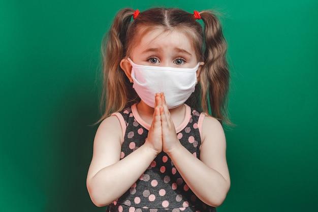 Кавказская больная маленькая девочка в медицинской маске во время эпидемии коронавируса молится на зеленом фоне крупным планом 2021