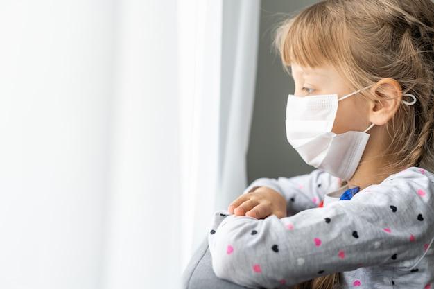 코로나바이러스 전염병 동안 의료 마스크를 쓴 백인 아픈 어린 소녀가 기도한다