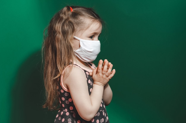 Caucasian sick little girl in medical mask during coronavirus epidemic prays on green background closeup 2021.copy space.