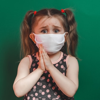 Caucasian sick little girl in medical mask during coronavirus epidemic prays on green background closeup 2021